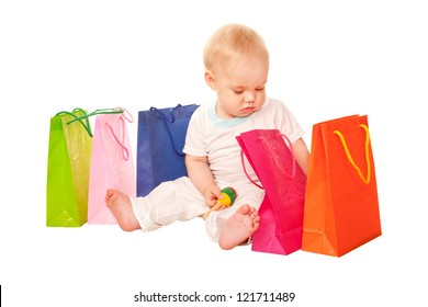 Baby shopping. Happy child sitting with shopping bags, examining purchase. Isolated on white background