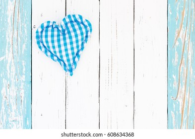 Baby shower boy background, turquoise heart shape with white and pastel blue wood and copy space.