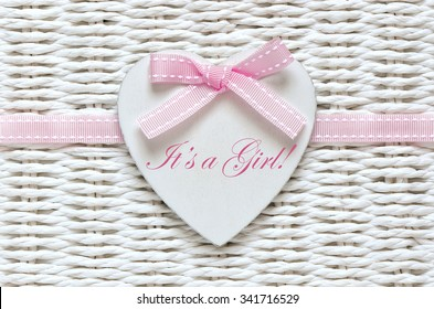 Baby shower card or invitation for baby girl with white wooden decorative heart with text on it