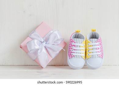 Baby shower concept with gift and baby's bootees, close-up