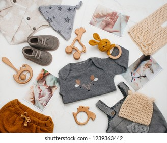 Baby shower concept. Newborn baby clothing, wooden toys and baby photos on white marble background. Top view, flat lay.