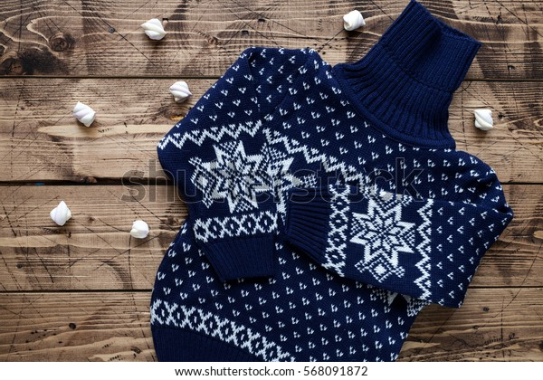 Baby shower concept on wood background - kid's winter sweater
