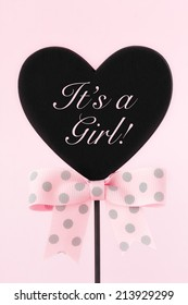 Baby shower decoration - It's a girl written on a heart shaped wooden blackboard decorated with a pink  bow