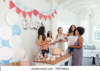 Baby shower. Group of diverse women together at baby shower. Smiling young pregnant woman celebrating baby shower with best friends.