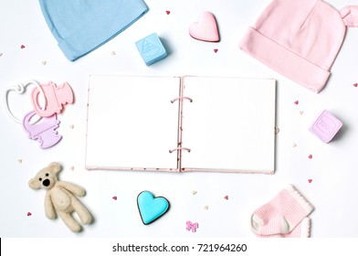 Baby shower party background with baby accessories and open empty book on white background with blank space for text; top view, flat lay