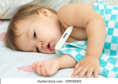 Baby sick with measuring electric thermometer. Child fever ill. Kid catch cold with temperature. Sick child in bed with fever measuring temperature with medical thermometer.