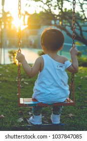 Baby sit on chain swing and look at sunset. vintage filter