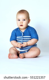 Baby sits on a gray background