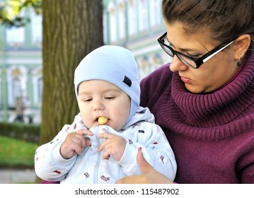 Baby sits on mother lap and eats corn ball