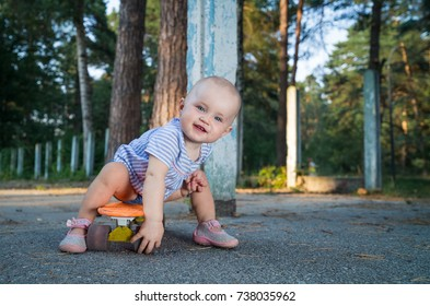 Baby sits on a skateboard.