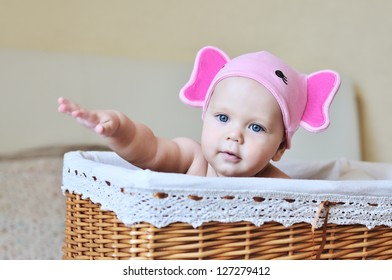 baby sitting in basket and showing something with hand