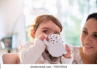 A baby sitting in a baby chair drinks in his special cup under his mother's gaze
