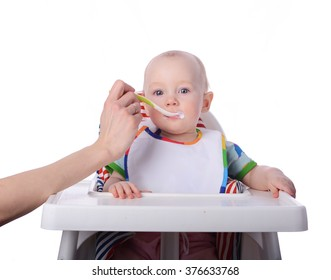 baby is sitting in the chair and eating jogurt