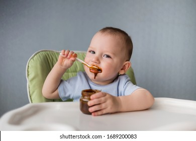 the baby is sitting in a high chair and eating food with a spoon