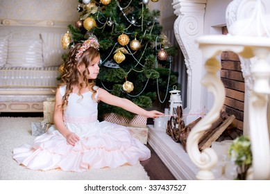 baby sitting near the Christmas fireplace and makes a wish with the help of a magic wand at home