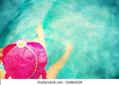 Baby sitting near swimming pool.