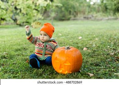 Baby sitting next to lit Halloween pumpkin holding leaf