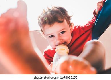 Bebé sentado en el balcón de su casa al sol bebe leche de una botella sola.