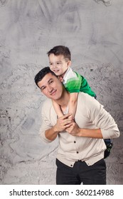 Baby sitting on father neck on white background