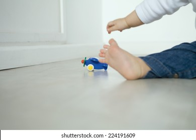 Baby sitting on floor, reaching for toy airplane, low section