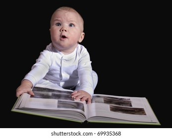 The baby sitting on the floor and read a great book