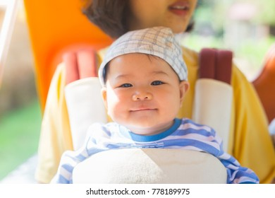 the baby is sitting on hip seat that can prevent injuries while holding the baby.