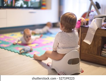 Baby sitting on the potty in the living room and watch TV. With her sisters, twins