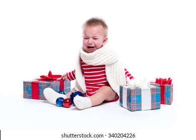 baby sitting on the priest on a white background in a striped white-red suit and a white scarf and tearfully crying and looking into the camera surrounded by blue gifts and Christmas decorations