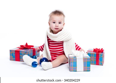 baby sitting on the priest on a white background in a striped white-red suit and a white scarf with a smile, looking into the camera surrounded by red and blue New Year's gifts, Christmas decorations.