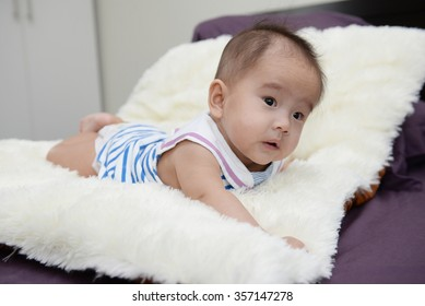 Baby sitting on a soft cloth in the living room.