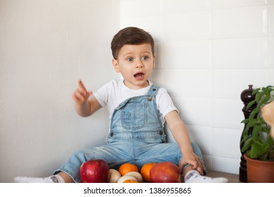 baby sitting on a table with fruit