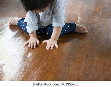 Baby is sitting on the wood floor, play and learn time