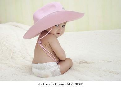 6d4d86d63d5 baby sitting in a pink cowboy hat