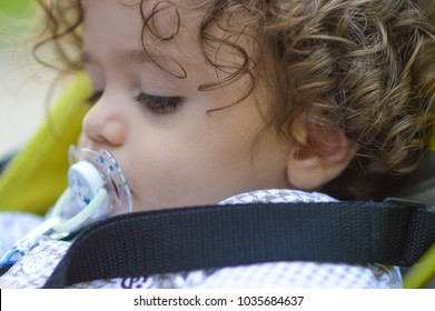 Baby in sitting stroller with pacifier