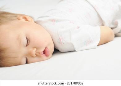 Baby sleeping in bed portrait, daytime sleep, child health care
