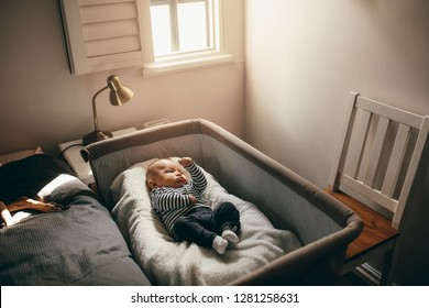 Baby sleeping in a bedside bassinet in bedroom. Infant lying on a crib moving his hands and legs.