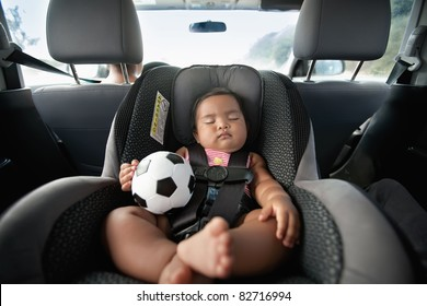 baby sleeping in car seat and holding a soccer ball