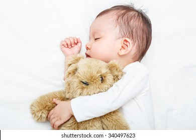 Baby sleeping with her teddy bear, new family and love concept