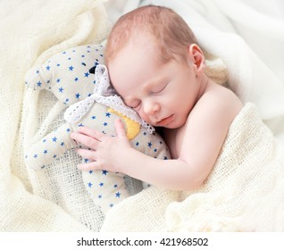 Baby sleeping with her teddy bear. New born relax in a white bedroom. Family at home. Love, trust and tenderness concept. Bedding and textile for nursery.