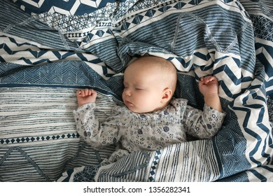baby is sleeping on the bed, dark blue bedding with an ornament. Lifestyle and casual style. top view