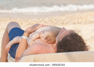 Baby sleeping on his father's chest on the beach near the sea.