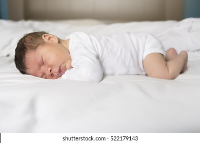 A Baby sleeping on white sheet at home