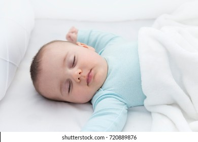 Baby sleeping with open arms and without pacifier in a cradle. Light blue pajama and white bed sheets.