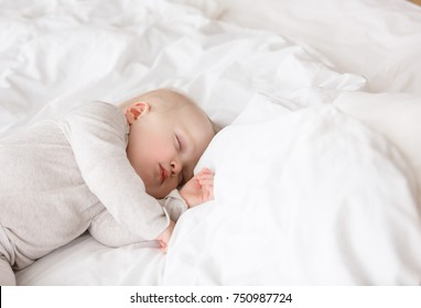 Baby sleeping with open arms and without pacifier in a cradle. White pajama and white bed sheets.