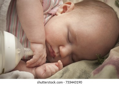 baby sleeping with a small bottle of food in his hand