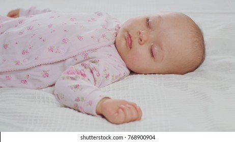 A baby sleeping sound on a white bed at home. Medium dolly shot.