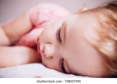 Baby sleeping sweetly on the bed close up face