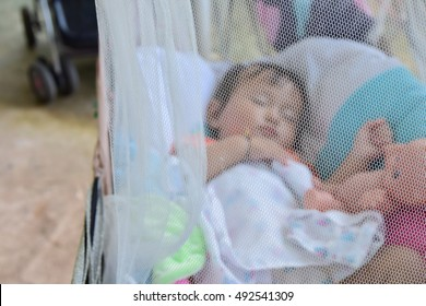 baby sleeping under a mosquito nets in cradle ,selected focus