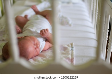 Baby sleeping in white crib