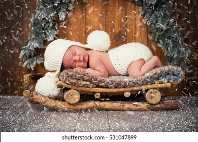 The baby is sleeping in wooden sledges. New year's Eve